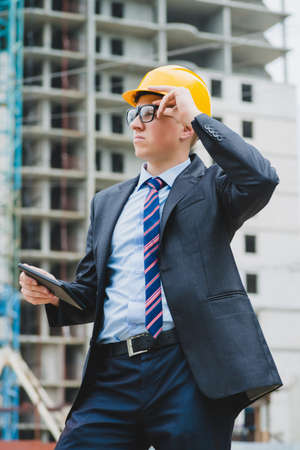 Young successful engineer in a helmet with a digital tablet photo
