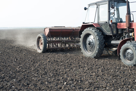 seed drill: Farmer in tractor sowing crops at field with seed scattering agricult
