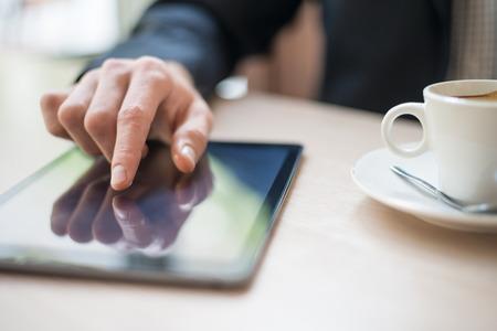 Mann mit Tablet-Computer das Lesen von Nachrichten am Morgen im Café