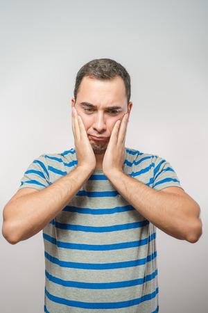 raised eyebrow: Caucasian man holds his head Stock Photo