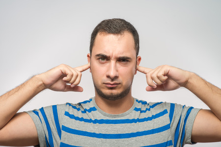 deafening: Closeup portrait young, angry, unhappy, stressed man covering his ears
