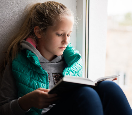 serious young, beautiful girl holding an open book