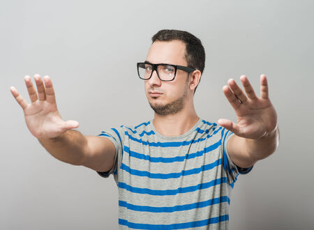 A young man in glasses showing stop photo