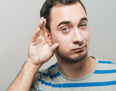 Man holds his hand near his ear and listening something photo