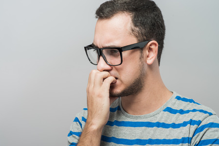 obsessive compulsive: Closeup portrait of a nerdy young guy with glasses biting his nails