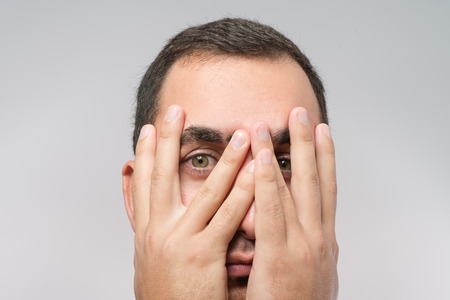 Young Caucasian man hiding his face with hand photo