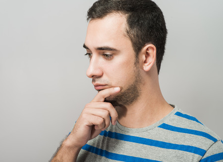 holding the head: Depressed young man  holding head in hands Stock Photo