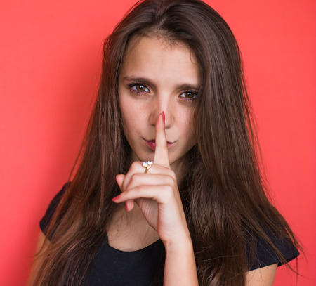 Secret woman. Female showing hand silence sign photo