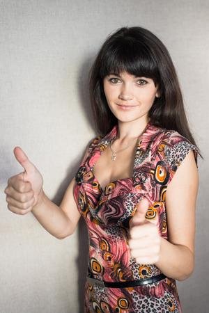 erfolgreiche frau: Eine junge, erfolgreiche Frau h�lt den Daumen nach oben.
