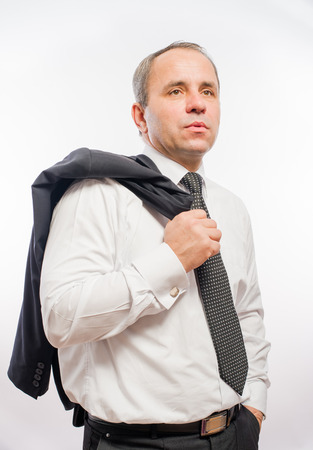 business man holding his jacket over his shoulder and a hand in his pocket photo
