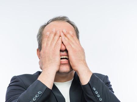 arrepentimiento: Hombre de negocios que cubre su rostro con ambas manos