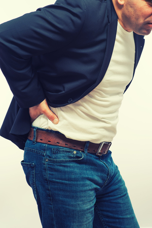 low back: Backache concept bending over in pain with hands holding lower back Stock Photo
