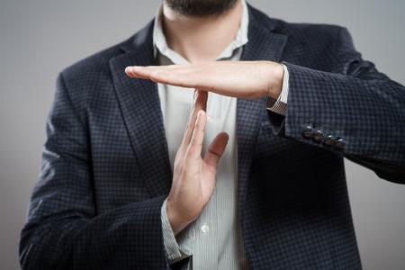 reunion de trabajo: joven hombre de negocios que muestra el tiempo hacia fuera la muestra con las manos contra Foto de archivo