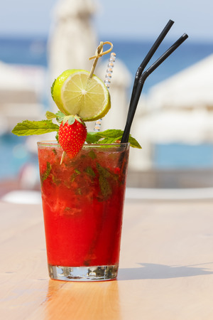 Strawberry cocktail on blurred beach background. Outdoor settings photo
