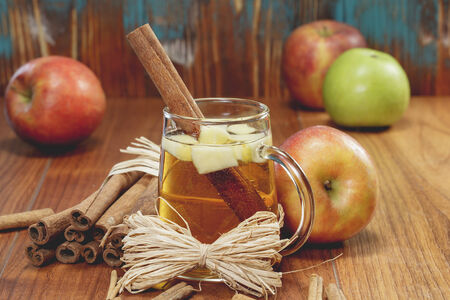 Winter drink with apples and spices on rustic wood. A macro photograph with shallow depth of field. Done with vintage retro filter. Imagens