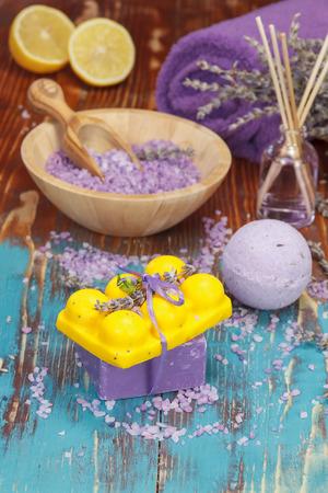 Lavender and lemon aromatherapy. Natural handmade lavender oil, soaps with bath salt, foaming bath bomb, lemon and lavender on wooden background. Macro, selective focus.