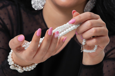 Beads pearls. Beautiful woman hands with pink manicure holding white pearl necklace.. Pearls and Nails concept photo