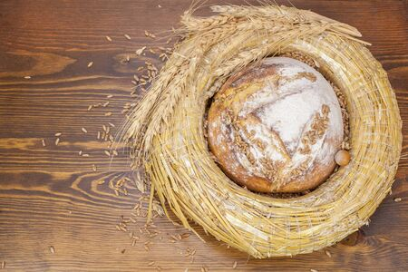 Bread. Fresh bread and wheat on the wooden background. photo