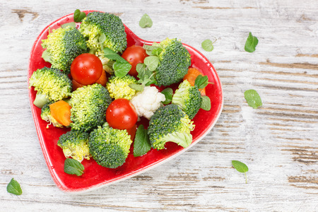 food dressing: Vegetables. Raw vegetable in heart shaped plate. Diet concept. Macrobiotic.