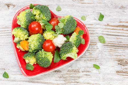 plato de comida: Verduras. Veh�culo sin procesar en la placa en forma de coraz�n. Concepto de la dieta. Macrobi�tica.