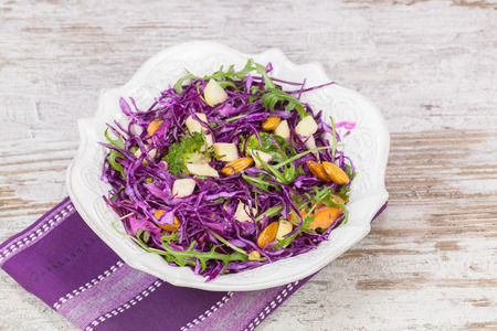 Cabbage salad. Red cabbage salad filled with nuts, broccoli , apples and fresh herbs. Macro, selective focus Imagens