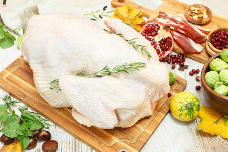 Whole raw turkey on wooden cutting board with vegetables, ham and spices.Preparing Thanksgiving Dinner with Turkey and ingredients such as bacon, vegetables, nuts, cranberries, pomegranate, spices photo