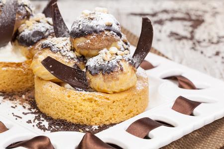 chuparse los dedos: Profiteroles. Un bollo de crema lleno de helado delicioso cubierto de rico chocolate. Macro, de cerca.