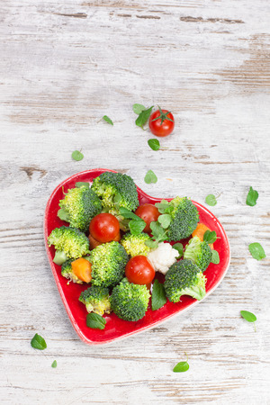 macrobiotic: Vegetables. Raw vegetable in heart shaped plate. Diet concept. Macrobiotic.