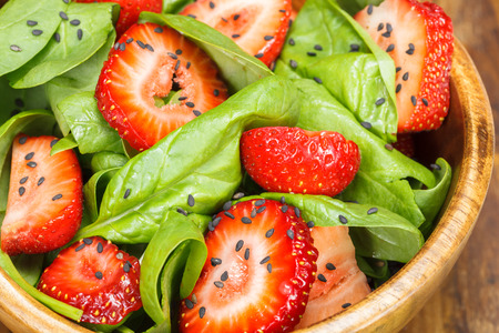 Strawberry  spinach salad . Strawberry Salad with spinach, poppy seed and sesame dressing. Space for text. Macro