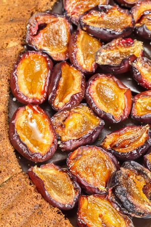 Plum tart. Plum cake with roasted cinnamon plums. Close up, macro. Above view photo