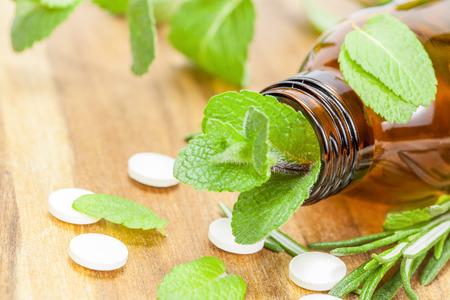 Medicación homeopática con tabletas. La medicina alternativa con las píldoras a base de hierbas y homeopáticos Botella con las tabletas y las hierbas en la mesa de madera