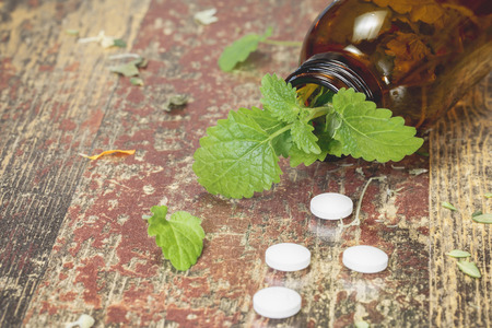 holistic therapy: Lemon Balm. Bottle with tablets and herbal on wooden table