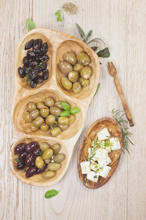 Black and green olives with feta cheese. Assorted olives and feta or goat cheese cheese in olive tree dish on wooden table photo