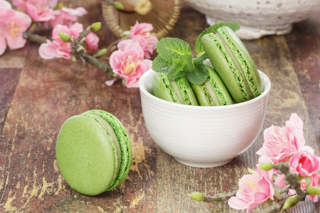 A teacup filled with matcha green tea macaroons with cherry blossom over rustic background.