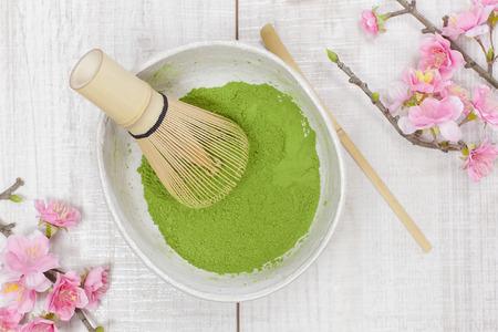 feier: Matcha Grüntee. Stilleben mit grünem Tee Pulver und Bambusbesen. Japanische Teezeremonie: Herstellung der pulverisierten Grüntees