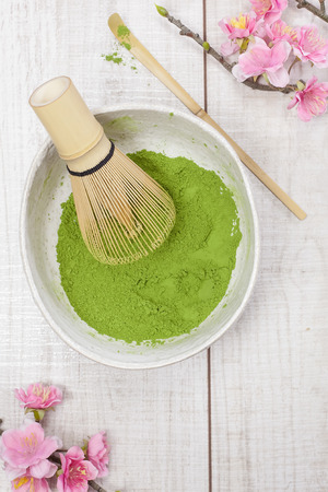 Matcha green tea . Still life with green tea powder and bamboo whisk. Japanese Tea Ceremony: Preparation of powdered green tea
