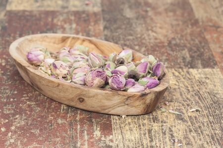 bourgeon: Pretty little edible violet rose buds, on old wooden table .  Stock Photo