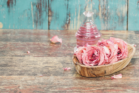Essential oil with roses on rustic wooden background.  Imagens