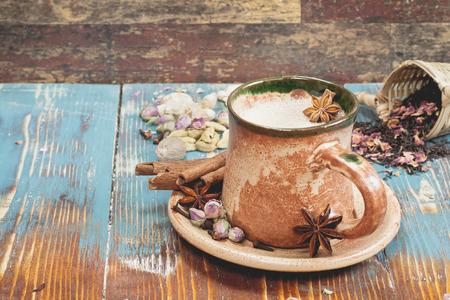 jengibre: Chai Masala. Chai masala India té con especias y leche en el fondo rústico. Macro, enfoque selectivo