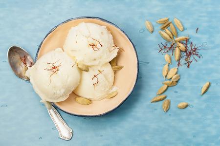 サフランとカルダモン アイス クリーム。サフランとカルダモン アイス クリーム小さな青いテーブル上ボウルします。トップ ビュー