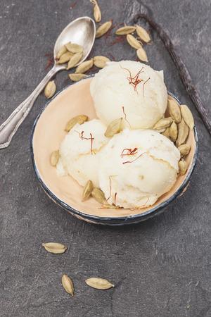 Saffron, cardamom and vanilla ice cream. Saffron, cardamom and vanilla bean ice cream in small rustic bowl over dark background Standard-Bild