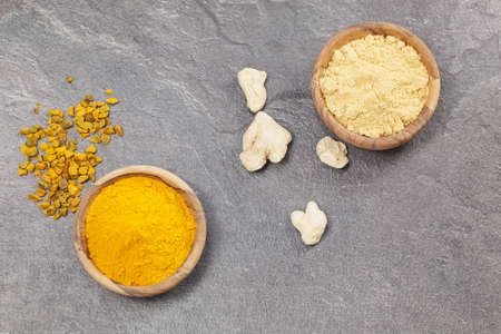 Ginger And Turmeric. Ginger powder and root and turmeric pieces and powder in olive wood bowls over dark granite table. Macro photograph, selective focus, focus on turmeric.