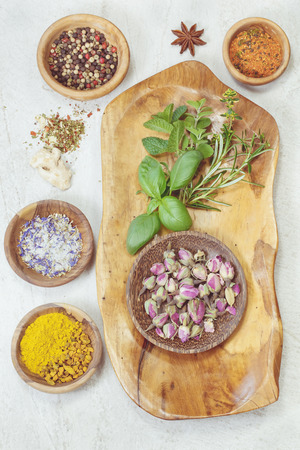 Assorted spices with fresh herbs in olive wood bowls over  granite table. Macro photograph, selective focus