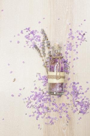 Lavender essential oil in a glass bottle. Aromatherapy lavender bath salt and massage oil on wooden background Standard-Bild