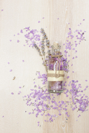 Lavender essential oil in a glass bottle. Aromatherapy lavender bath salt and massage oil on wooden background Imagens