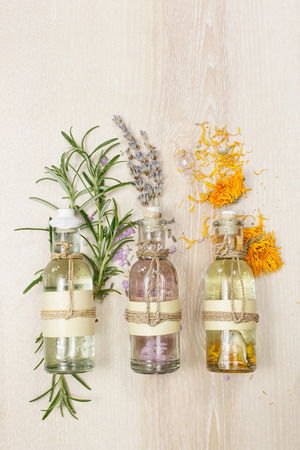 wooden aromatherapy: Aromatherapy massage oils. Row of essential oils in glass bottles rosemary lavender and calendula  on the wooden board.