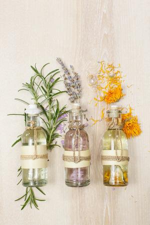 Huiles de massage aromathérapie. Ligne d'huiles essentielles dans des bouteilles en verre de lavande et de romarin calendula sur la planche de bois. Banque d'images
