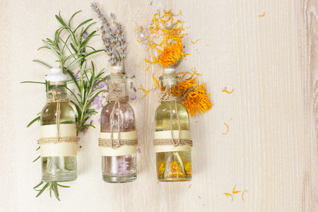 Aromatherapy massage oils. Row of essential oils in glass bottles rosemary lavender and calendula  on the wooden board.
