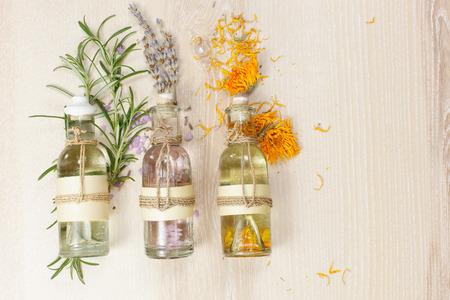 huile: Huiles de massage aromath�rapie. Ligne d'huiles essentielles dans des bouteilles en verre de lavande et de romarin calendula sur la planche de bois. Banque d'images