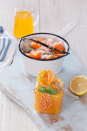 marillenmarmelade: Aprikosenmarmelade. Aprikosenmarmelade in Vorbereitung. Gezuckerte Aprikosen in einen Topf und Aprikosensaft und Marmelade im Glas auf einem h�lzernen Oberfl�che. Macro, geringe Tiefensch�rfe. Nat�rliches Licht